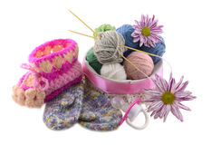 Baby knitted things. Baby knitted shoe and mittens with flowers, pacifier and knitting balls isolated Royalty Free Stock Photo
