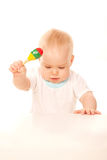 Baby knocking his rattle on the table. Stock Photo