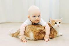 Baby kriecht Spiele mit Katzenhaus auf Boden lizenzfreie stockfotografie