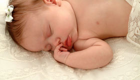 Baby on Lace. Sleeping baby with lace coverlet and bow in hair royalty free stock images