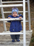 Baby on a ladder. The child on a ladder (a theme: ascentions on a career ladder in execution of the one-year-old child Royalty Free Stock Photos