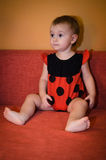 Baby in ladybird costume plays on the couch Royalty Free Stock Images