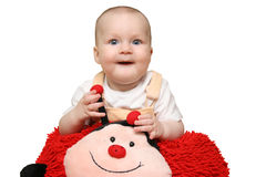 Baby with ladybug pillow Stock Image
