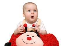 Baby with ladybug pillow Stock Photos