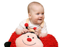 Baby with ladybug pillow Stock Photo
