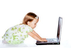 Baby and laptop. Baby girl typing on the computer Royalty Free Stock Images
