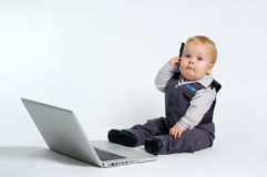 Baby with laptop. Blond baby in suit working with laptop Royalty Free Stock Image