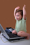 Baby with laptop and arms in air Stock Images