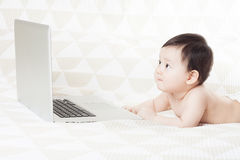 Baby and laptop Stock Images