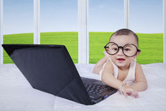 Baby with laptop laughing on bed Royalty Free Stock Photos