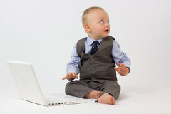 Baby with Laptop Looks into Copy Space Royalty Free Stock Image