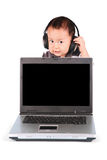 Baby with laptop and wearing headphones Stock Photography