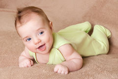 Baby laugh. Pretty young baby lying on towel and laugh with mouth open Royalty Free Stock Photo