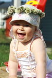 Baby laughing. Baby girl sitting outside in the sand box and laughing with a clover wreath on the head Stock Photography