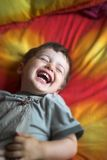 Baby laughing. Baby close up laughing on red and yellow bed stock image