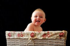 Baby is laughing in the basket Stock Photo