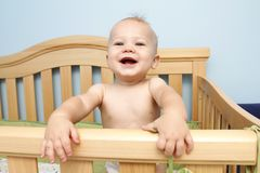 Baby laughing in crib. Baby boy standing and laughing in crib stock photography