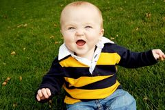 Baby Laughing in the Fall. Cute baby boy with an adorable expression sitting in grass Royalty Free Stock Images