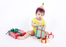 Baby laughing wearing party hat, little baby celebrate with heap of gift boxes. Royalty Free Stock Image