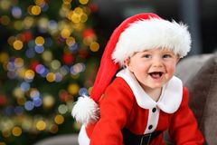 Baby laughing wearing santa disguise in christmas. Baby laughing wearing santa claus disguise on a couch at home in christmas with a tree in the background stock image