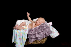 Baby in Laundry. A baby in a laundry basket with her clothes hanging off the sides stock photos