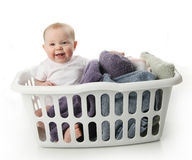 Baby in a laundry basket. Portrait of an adorable baby sitting in a laundry basket with towels Stock Photos