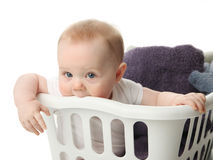 Baby in a laundry basket. Portrait of an adorable baby sitting in a laundry basket with towels Royalty Free Stock Image