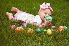 Baby Lay Eggs. Baby girl laying in the grass with an assortment of colored Easter eggs Royalty Free Stock Photo