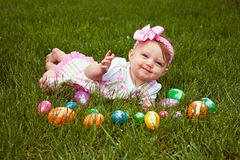 Baby Lay Eggs Wave. Beautiful baby laying in grass with an assortment of colored Easter eggs Stock Photography