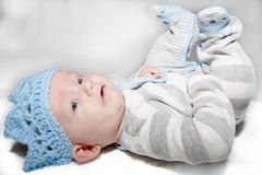 Baby Laying on Back Wearing Blue Knit Crown. Baby with blue eyes lying on his back looking to the side with a thoughtful and happy expression wearing a light Stock Image