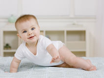 Baby laying on bed Stock Photography