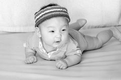 Baby laying on bed with cute expression Stock Image