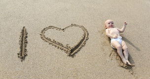 Baby laying down in the heart shape print on the sand. Stock Photography