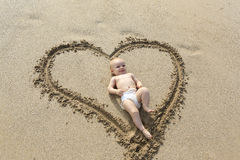 Baby laying down in the heart shape print on the sand. Royalty Free Stock Image