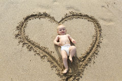 Baby laying down in the heart shape print on the sand. Stock Photo