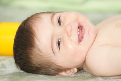 Baby laying down on rug Royalty Free Stock Photos