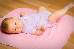 Baby laying on floor Stock Photography
