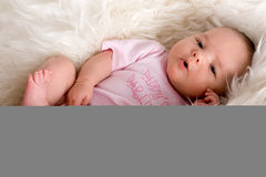 Baby laying in a sheepskin. In a body looking happy Royalty Free Stock Photos