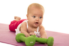 Baby laying on stomach with green weights Royalty Free Stock Photo