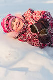 Baby lays on snow and laugh Stock Photography