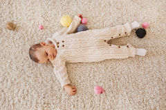 Baby lays on the white shaggy carpet. Top view Royalty Free Stock Image