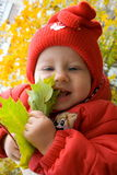 Baby with leaf. Baby in red shirt with leaf in hand Royalty Free Stock Photo