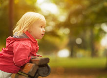 Baby leaning on bench and looking on copy space Royalty Free Stock Image