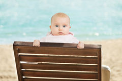 Baby Leaning On Deckchair On Beach. Portrait Of An Innocent Baby Leaning On Wooden Bench On Beach Royalty Free Stock Image