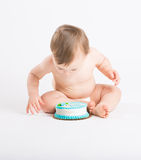 Baby Leaning in to Eat Cake. A cute 1 year old sits in a white studio setting. The boy is very excited to start eating his birthday cake. He is only dressed in a Royalty Free Stock Image