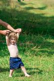 Baby learn to walk. A little boy helps to learn how to walk by the hand of his father Stock Image