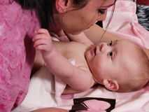 Baby Learning. Mother in a pink shirt leans over her new baby Royalty Free Stock Photos
