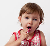 Baby learning to care about her teeth with toothbrush Royalty Free Stock Image