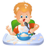 Baby is learning to eat. A picture of a boy sitting on the chair at the table and eating  porridge Royalty Free Stock Image