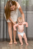 Baby learning to walk. With help and support of mother's hands. First Steps royalty free stock photography